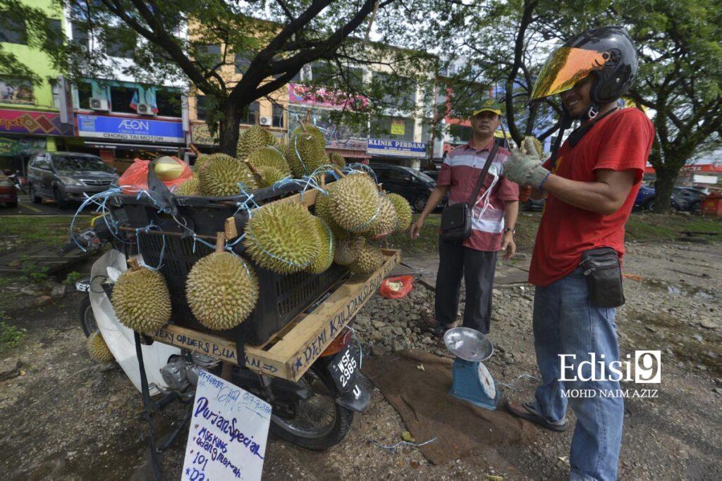 ADE FIRDAUS melayan salah seorang pelanggannya sejurus tiba di bahu jalan utama Sungai Buloh- Kuala Selangor di sini semalam.