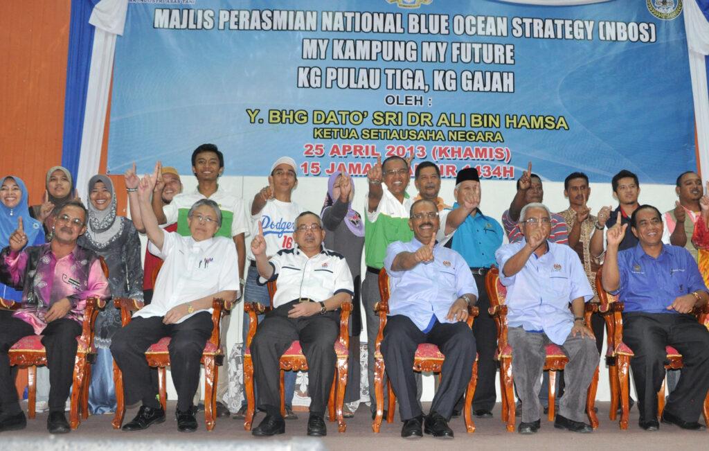 Penulis (berdiri tengah) bersama  Ali Hamsa dan pegawai-pegawai kanan kerajaan ketika pelancaran program MKMF Mukim Pulau Tiga, Kampung Gajah, pada 25 April 2013.
